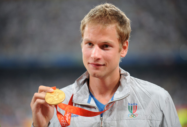 (FILES) Photo taken on August 22, 2008 shows Italy's Alex Schwazer posing with his gold medal on the podium of the men's 50 km walk of the 2008 Beijing Olympic Games. Italy's reigning 50km walk champion Schwazer has been withdrawn from the London 2012 Olympic games for failing a drugs test, a source with knowledge of the case confirmed to AFP on August 6, 2012. AFP PHOTO / FABRICE COFFRINI (Photo credit should read FABRICE COFFRINI/AFP/GettyImages)